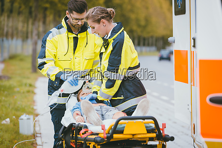 emergency doctor giving oxygen to accident