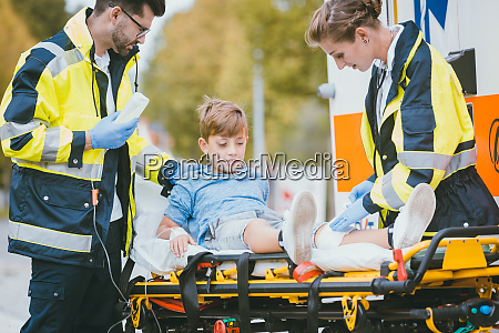 medics putting injured boy on stretcher