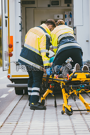 paramedic on stretcher fighting for life