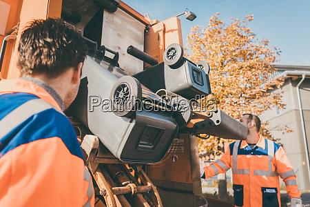 worker emptying dustbin into waste vehicle