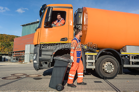 two garbagemen working together on emptying