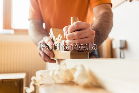 young carpenter working with wood planer