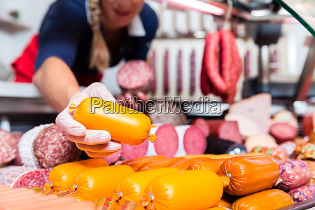 butcher shop woman holding meat in