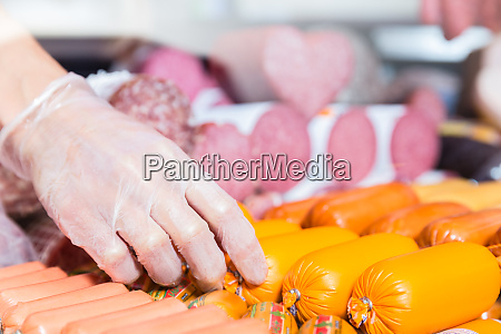 woman putting sausages and meat in