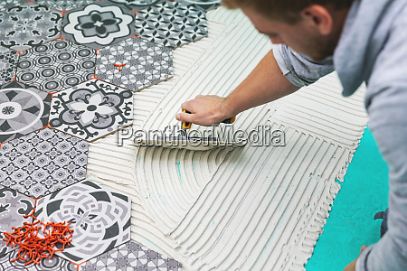 worker applying tile adhesive on the