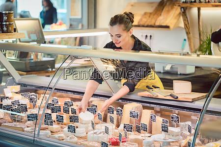 shop clerk woman sorting cheese in