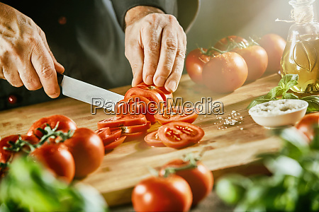 cook chopping bright red tomatoes on