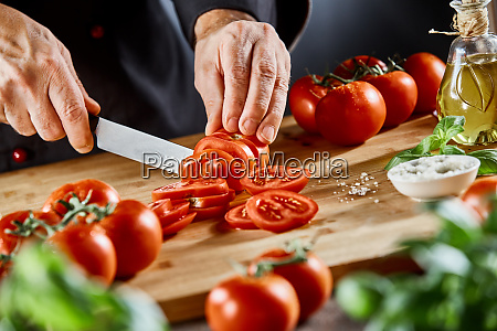 chef slicing fresh ripe tomatoes on