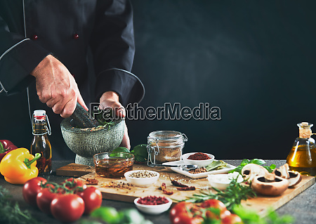 chef grinding herbs next to seasoning