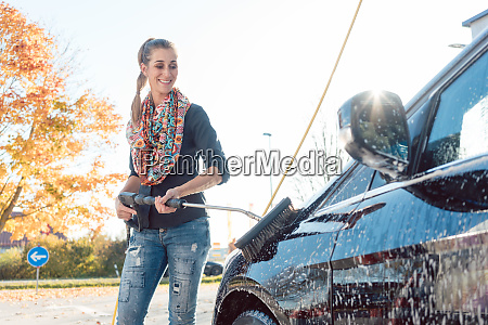 woman cleaning her vehicle in self