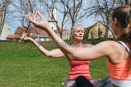 mother and adult daughter in yoga