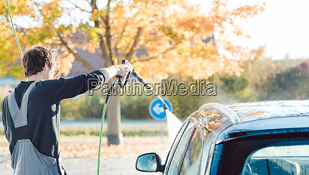 worker cleaning car with high pressure