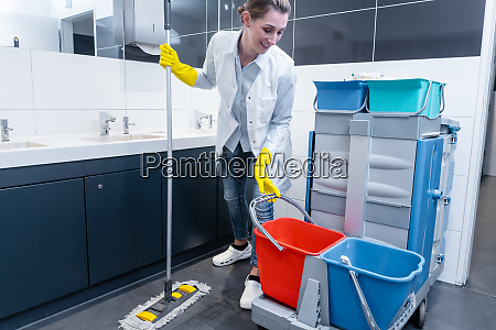 cleaning lady mopping the floor in