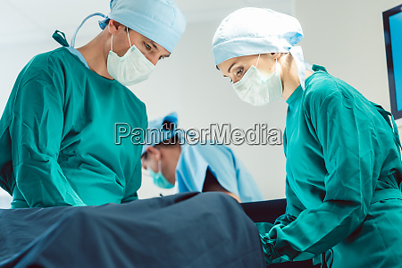 doctors and surgeons operating patient in