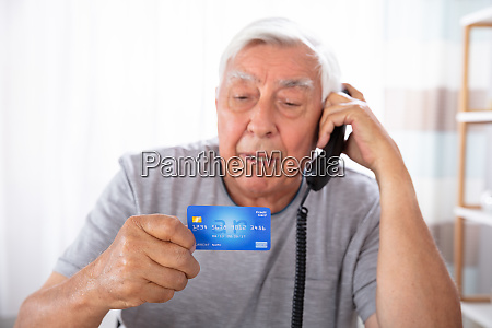 man with credit card using landline