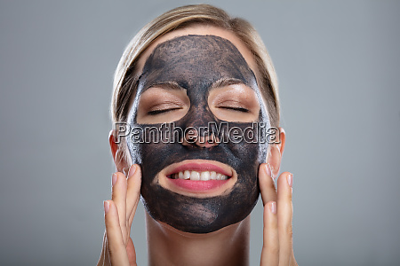 happy woman using activated charcoal face