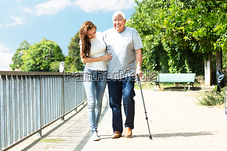 woman assisting her father while walking
