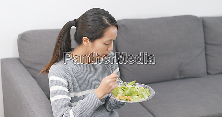 woman eating salad at home
