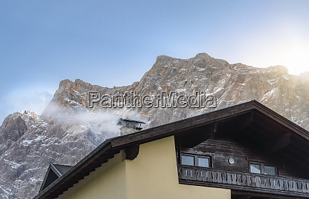 smoky chimney and the snowy alps