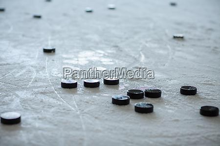 pucks on empty ice rink