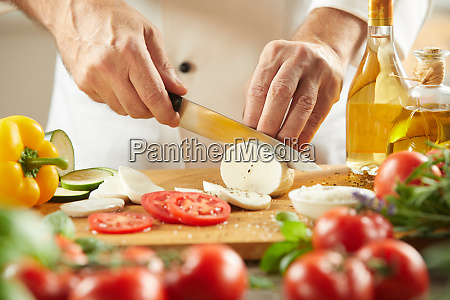 chef cutting fresh cheese with tomatoes