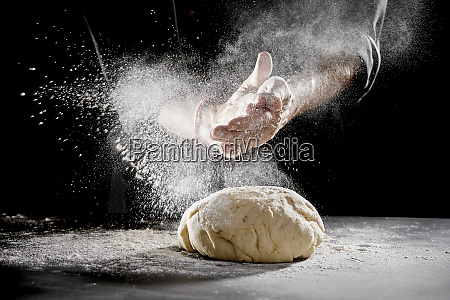 chef scattering flour while kneading dough