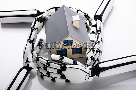 robot hands protecting house model