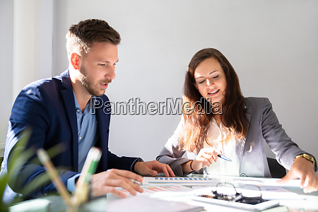two businesspeople analyzing graph