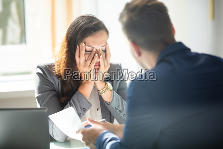 businessman showing document to female employee