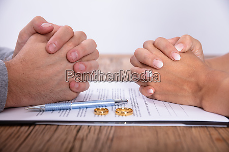 couples hand with divorce agreement and