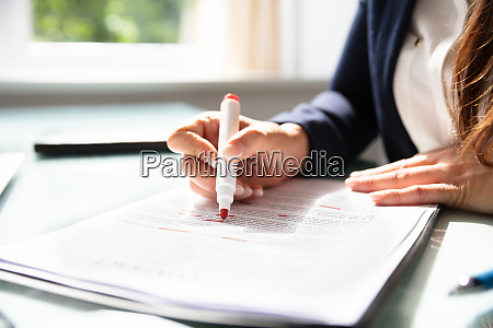 businesswoman marking error in contract form