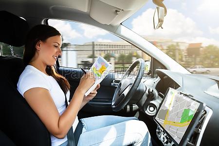 woman sitting inside car writing schedule