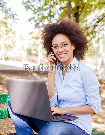 happy african woman working with laptop
