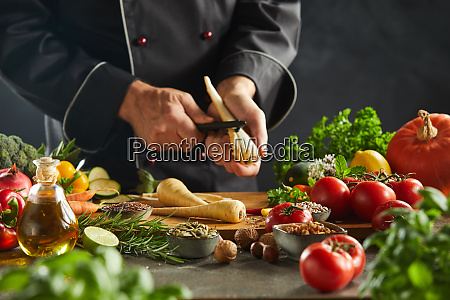 adult chef peeling carrot above cutting