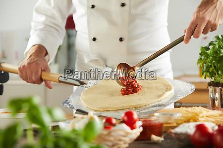 chef ladling tomato paste onto a