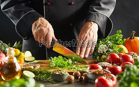 restaurant worker cutting up green leafy