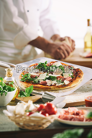 chef preparing a pizza with fresh