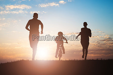 parents running with their child riding