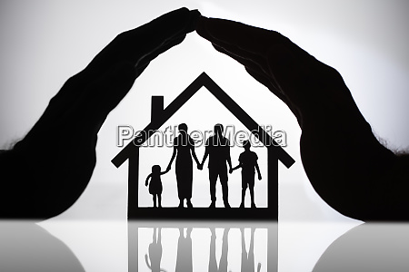 person protecting house with family figures