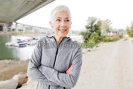 smiling senior woman with earphones listening