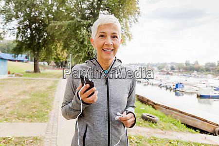 active senior running woman listening music