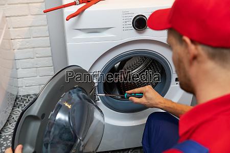 repairman with screwdriver repairing washing machine