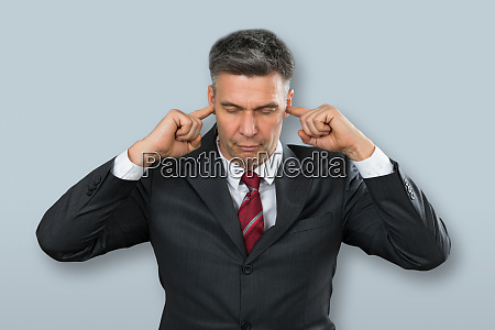 businessman with eyes closed and fingers