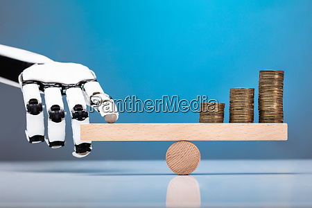 robot balancing stacked coins with finger