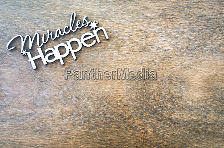 inscription miracles happen on a wooden