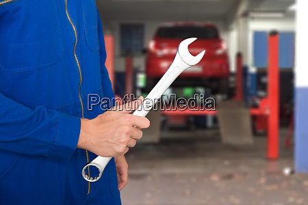 car mechanic holding spanner
