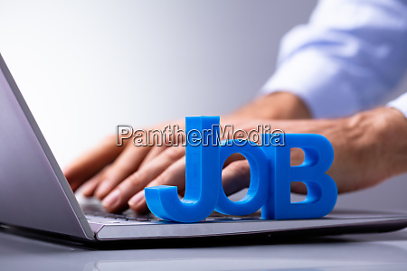 businesspersons hand using laptop