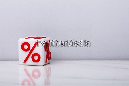 white cubic block with red percentage