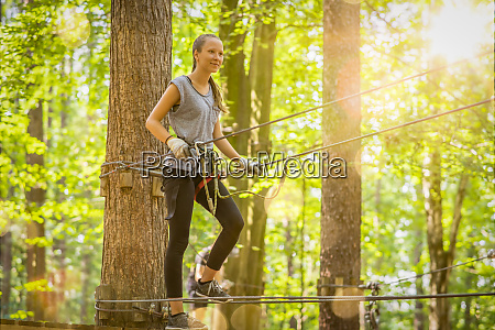 young blond girl climbs in summer