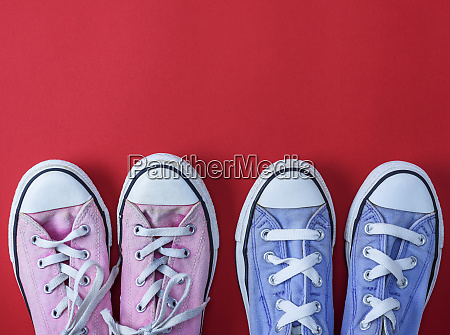 two pairs of worn textile sneakers